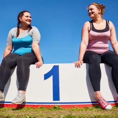 Dos mujeres después de hacer ejercicio sentadas en un podium